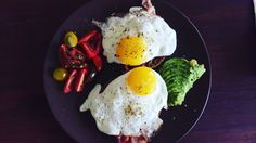 Fried egg on bread with avocado, bacon and tomatoes