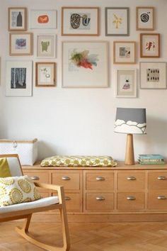Wall pictures grouped together above a low storage unit, table lamp and wooden rocking chair