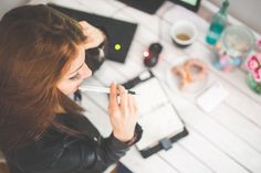 Young woman thinking with pen while working / studying at her desk · Free Stock Photo