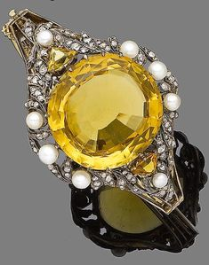 A late 19th century citrine, pearl and diamond bangle, circa 1890 The circular mixed-cut citrine within a surround set with 4.1-5.0mm pearls and rose-cut diamonds, the shoulders accented with triangular-cut citrines, to a hinged bangle, pearls untested, inner diameter 6.5cm
