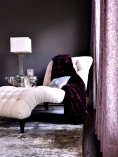 """In this glamorous, contemporary master suite, dark walls create the perfect backdrop to a white chaise lounge. """"We defined the seating area with a richly-textured rug and added a fur throw blanket and sequined throw pillow to create the feeling the clients were looking for,"""" says designer Nina Magon."""