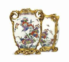 A PAIR OF LOUIS XV ORMOLU-MOUNTED MEISSEN (AUGUSTUS REX) PORCELAIN VASES  THE PORCELAIN CIRCA 1730, BLUE AR MONOGRAM MARKS, THE MOUNTS CIRCA 1740-50  Each decorated with polychrome flowers and butterflies, with foliate scrolled arms on a pierced shell-cast base  15¾ in. (40 cm.) high (2)