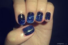 Sparkly blue nails reminiscent of a galaxy full of stars.