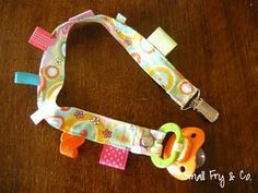 a taggie binkie clip (combining the usefulness of a binkie clip with the interest of tags and ribbons).