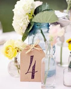 The Centerpieces ~ Tag-shaped cards sported rubber-stamped table numbers. They rested upon against mix-and-match vessels holding assorted flowers.