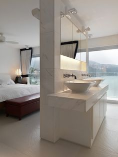 Beachfront House with partial wall separating master bathroom and bedroom areas by Original Vision