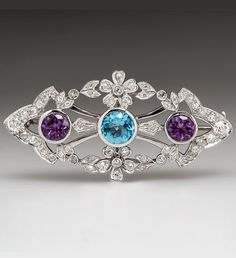 An Art Deco platinum, diamond, topaz and amethyst brooch. Set with 1.28 carats of old European-cut diamonds, centring a bezel set round-cut blue topaz, flanked by bezel set amethysts, mounted in platinum. #ArtDeco #brooch
