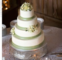 Simple, elegant, and natural, the four-tiered wedding cake was frosted with buttercream, trimmed with sage green ribbon, and accented with faux yellow peonies.