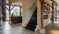 Een strakke stalen trap geeft achter de kastenwand van de keuken toegang tot de daarboven gelegen studie.