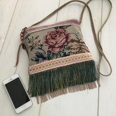 Small cross body bag in vintage style made of a jacquard fabric with roses combined with a plain fabric in old pink at the backside. This small purse is provided with fringes and ribbons and a bead strand. It closes with a zipper and is lined with a beige cotton fabric. It is made water and dirt resistant. Should it be cleaned, dry cleaning is recommended. This is really a handmade one of a kind item, so dont be too late! Style: bohemian, vintage, shabby chic Materials: jacquard fabrics…