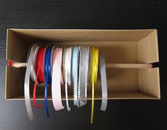 SHOEBOX RIBBON ORGANIZER:  This was a really quick project, but it'll make a difference in my efforts to clean up my crafting space. Basically, slots are created in the shoebox for a dowel that holds the spools of ribbon. Colorful buttons help keep the dowel from easily sliding out of the slots. The ends of the ribbons hang out from under the lid of the box making them easily accessible while not unwinding everywhere.