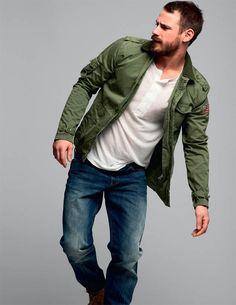 Men's Fashion: Green Jacket, White Henley & Jeans.