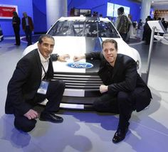 Brad Keselowski, right, and director of Ford Racing Jamie Allison pose with a replica of Keselowski's new race car Wednesday at Cobo Center.