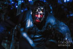 Dark halloween photograph on the face of an evil zombie man creeping though black shadows at the dead on night by Ryan Jorgensen