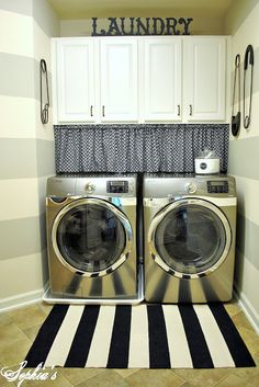 """A washer and dryer fill most of the space in this room, and a corner niche holds cleaning supplies in budget-friendly flea market containers. Click through for the """"before"""" shot from this laundry room makeover and more ideas for organizing your laundry room."""