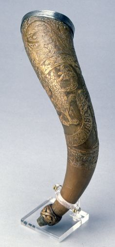 Drinking Horn; carved in medieval manner; low relief; depicts king and two lions; silver band and medallions containing birds and beasts around mouth; inscribed.