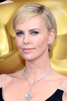 Charlize Theron, with her signature ultra-blonde crop, brushed to one side, along with peachy lips and cheeks and lightly defined eyes, Theron is simple yet breathtaking. Story featured on Harpers Bazaar #Bazaar #Oscars2014 #Beautylooksofthenight