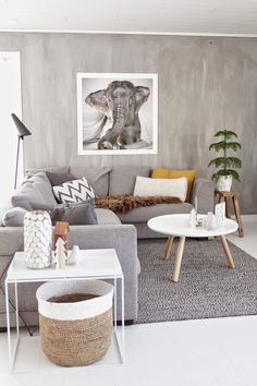 canapé d'angle gris, table basse en bois et blanc scandinave, objets déco en bois et blanc et peinture grise dans le salon nordique