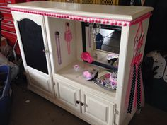 Upcycled entertainment center becomes little girl's dress up wardrobe.