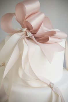 Simple fondant covered cake topped by beautiful cascading silk ribbon bow adorned with rhinestone accents
