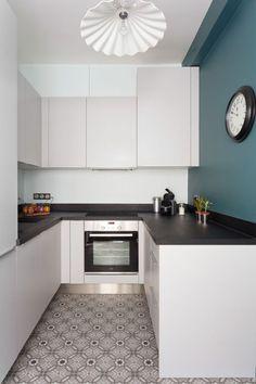 Une cuisine moderne, rythmée par le carrelage à motifs et un bleu profond sur le mur