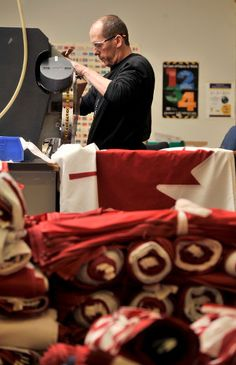 John Baker operates a grommet machine during his shift at Flags Unlimited in Barrie. MARK WANZEL PHOTO Canadian Flags, National Symbols, News Stories