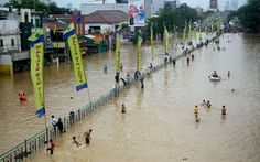 People wade through floodwaters in Jakarta, Indonesia Jan 2013