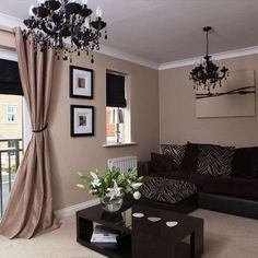 The paint color with white trim with picture frames with black border , the flowers of choice in the room and heavy curtain style that seems very cozy and home sweet home