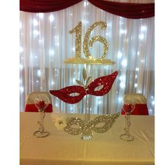 3. GLITZY HEAD TABLE DECOR You deserve to be the center of attention at your Quinceanera so it's important to carefully decorate the head table. Adding glitter to your masquerade decorations and placing a white backdrop with lights behind will look extra glitzy without breaking the bank.