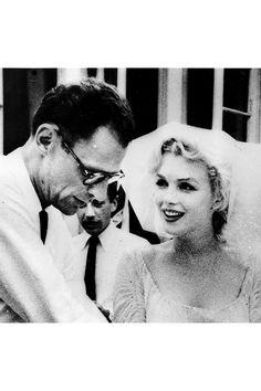 MARILYN MONROE/マリリン・モンロー:元大リーグ選手のジョー・ディマジオと1954年に2度目の結婚。ダークなペンシルドレスにファー襟のボウタイジャケット姿で、入籍手続きへ。©amanaimages