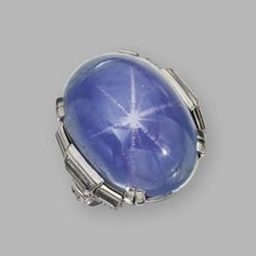 STAR SAPPHIRE AND DIAMOND RING,  CIRCA 1930. The cabochon star sapphire weighing approximately 75.00 carats, flanked by baguette, old European-cut and single-cut diamonds weighing approximately 1.75 carats, mounted in platinum