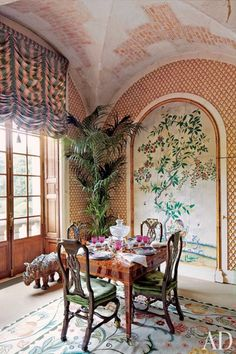 At Valentino Garavani's French estate, Château de Wideville, Portuguese chairs surround a Piedmontese dining table in the winter garden—the fashion designer's favorite spot at the grand residence. The panel that fills the arched niche is from China, a country that fascinates Valentino and inspired much of the home's decoration.