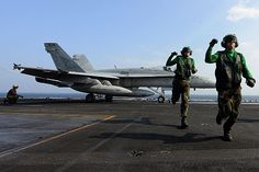 (Dec. 11, 2012) Aviation Boatswain's Mate (Equipment) 3rd Class Justin Bryan and Aviation Boatswain's Mate (Equipment) Airman Matthew Fulks clear the launching area as an F/A-18C Hornet from the Warhawks of Strike Fighter Squadron (VFA) 97 prepares to launch from the aircraft carrier USS John C. Stennis (CVN 74).