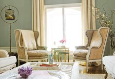 Large, luxurious armchairs in Parisian living space with tufted ottoman and small purple flowers