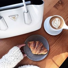 White Prada Saffiano tote, croissant and coffee art.