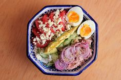 Lettuce and cucumber topped with tomato and feta cheese; avocado; tuna, red onion and sesame seeds; egg