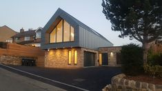 Blue Zinc Cladding on buff brick in an residential street scene. The Glazed gable allows for long views across the neighbouring agricultural land. Zinc Cladding, External Cladding, House Cladding, Gable House, Cabin House Plans, Garage Renovation, Cabin Homes, Modern Architecture, Brick