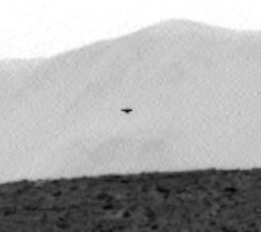 "Video: Dark Triangle UFO On Mars Caught By Curiosity Rover, July 2014 ""This triangle UFO was caught by the rover this week in photo Sol 688. I say triangle, because it looks like a TR3B from a distance. The ball in its center and its shorter end…says that it could be a triangle with two points showing,"" says Scott Waring author of UFO Sightings Daily."