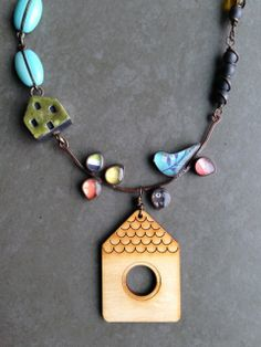 Wood House pendant- ArtChixStudio Resin and Copper Bird/Brance focal- Jade Scott Ceramic house- Elukka Glass beaded chain Matte Hematite rounds wire wrapped with brass wire Hear toggle- TheaToo  Meausres about 20-21 inches Â