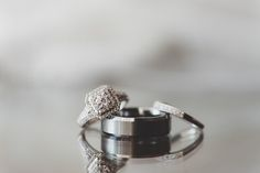 How I Got The Shot - diamond engagement ring, wedding band and grooms band sitting on a mirrored surface || Featuring: Brittani Elizabeth Photography
