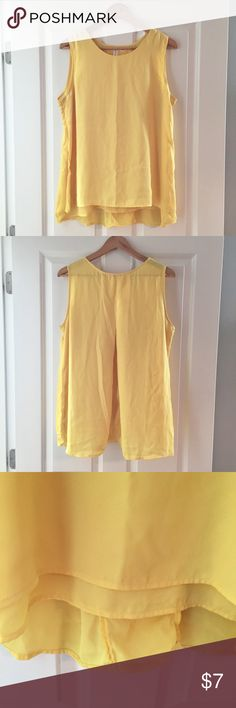 Tacera Flutter Chiffon Shell Lovely yellow sleeveless blouse with a double layer of chiffon in the front, eliminating sheerness and creating a feminine flow to the top. Back of top gathers at the top and opens to flow at the hem. VGUC. There is one tiny snag in the fabric in the back, shown in pic 5. Because of the flow of the top, it isn't visible until held flat. Bust 21, length 27. Tacera Tops Blouses