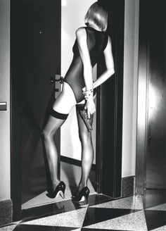 Woman with gun behind her back by Helmut Newton for Wolford Stockings, 1995