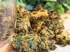 Smokey Chipotle Kale Crisps with fresh kale in background and a glass jar of kale chips on the left