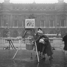 In 1956, you'd still hear the ring Salvation Army bell. Here, a woman collects donations outside the opera house.