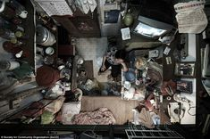 Pile it high: A woman sits in the only available space in her room. Campaign groups say many Hong Kong residents are being neglected by the ...