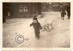 Dziecko ciągnące sanki przy budynku drewnianym przy ulicy Konopnickiej.W tle widoczna brama do KZN-ów.Lata 40 XX wieku.( fot.ze zbiorów Henryka Nikisza)