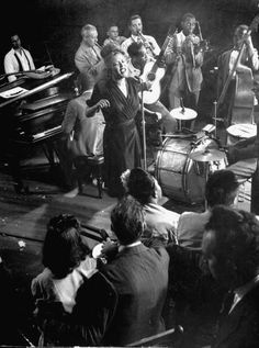 Billie Holiday singing Fine Mellow accompanied by Cozy Cole on drums James P Johnson at piano other unident musicians during jam session in studio of...