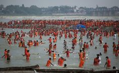 Hindu pilgrims, known as Kanwarias, take holy dips in the Ganges River in Allahabad, India, Sunday, July 15, 2012. Kanwarias are devotees performing a ritual pilgrimage in which they walk the roads of India, clad in saffron, and carrying ornately decorated canisters of sacred water from the Ganges River over their shoulders to take it back to Hindu temples in their hometowns, during the Hindu lunar month of Shravana.