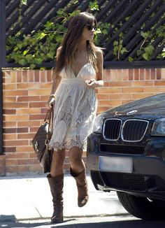 """Sara Carbonero in white dress and tall brown boots, accessorized with Louis Vuiitton """"Olympe Monogram"""" bag."""