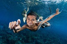 """""""A young village boy leaps from his dugout canoe and dives down to investigate me in my scuba gear, as I exhale bubbles and hold out my a huge underwater camera dome! The villagers are Alor, Indonesia continue to live off the sea, mostly fishing with hand-lines and handmade wooden fish traps. The joy and innocence of the children in these communities is inescapable."""" Photo and caption by Shawn Heinrichs/National Geographic Photo Contest"""